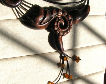 Hand carved wooden necklace with baltic amber