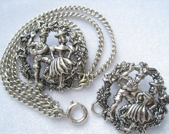 "SALE Sweater Guard Pin Set has 3 Chains.  1.25"" Round Pins have Floral Border around Dancing Bavarian Couple. 3-Chain Swag. Spring C-Clasp."