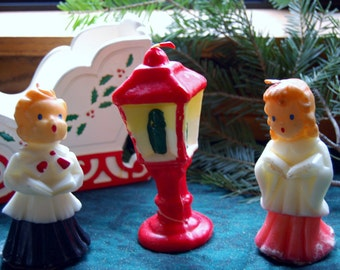 Vintage Christmas carolers candles. Wax candle figurines. Wooden sleigh. Vintage Christmas scene.
