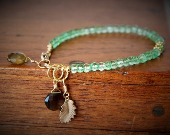 Zaira Bracelet: Tiny faceted green quartz beads strung w 14k gold filled findings, 14k gf leaf, beer quartz & smoky quartz briolette charms