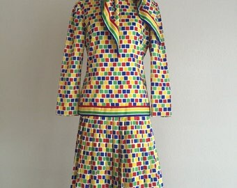 Vintage 1970's Carlye Multi colored suit with matching scarf/ head scarf. 3 pieces. Skirt falls beliw knee. Pleated shirt. Top zips up back.