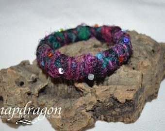 Sari silk yarn woven bangle embellished with seed beads.