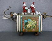 Assemblage circus sculpture.  One of a kind.  Elephant with porcelain head and tin body on castor wheels carrying clowns with trick dogs.