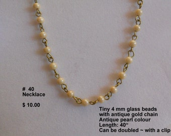 140 ~ Pretty and dainty necklace of creamy glass pearls, and antique gold links.  Slip over head fit.  40 in . long.
