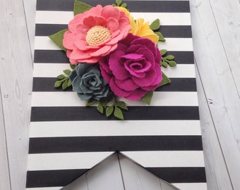 Black and white striped wall hanging with felt flower arrangement