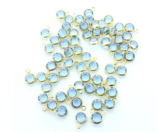 Swarovski 6mm (SS29) light sapphire channels in brass setting with 1 loop.  Price is for 10 channels