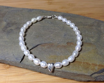 White cultured pearl bracelet with a sterling silver heart charm.