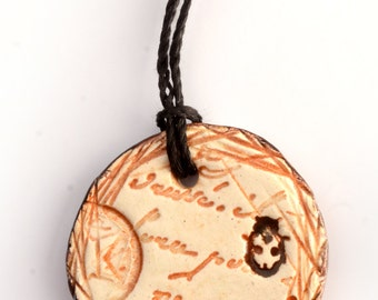 small ceramic pendant necklace with curse word and ladybug
