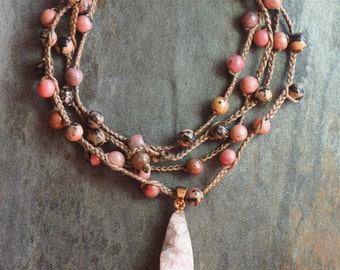 The necklace is braided in Rhodonite.