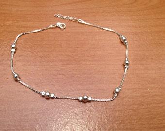 Silver ankle bracelet.