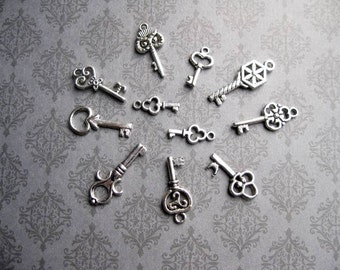 11 small key charms in silver tone - C2345