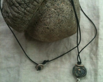 Necklace with a primitive vibe using stoneware and PMC on leather