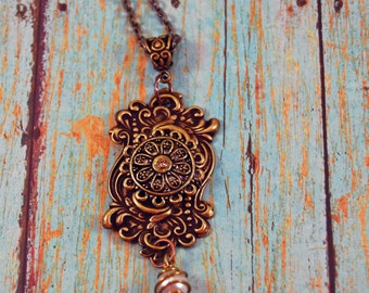 collaged, assemblage pendant with victorian nickel free brass stamping. Oxidized brass stampings with glass pearl dangle on 24 inch chain.