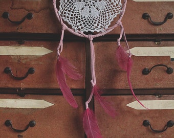 Pink dream catcher made with leather and feathers.
