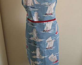 Attractive cotton Adult apron in a nautical theme in blue and white with red trim on the patch pocket.