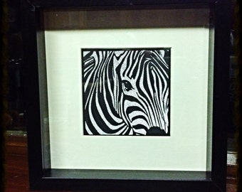 Zebra paper-cut with silver glittered background.