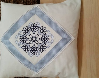 Pillow with curlicue embroidery and lace trim