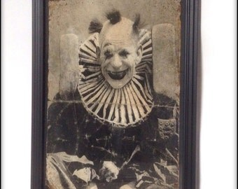 Aged reproduction Victorian creepy clown in frame.