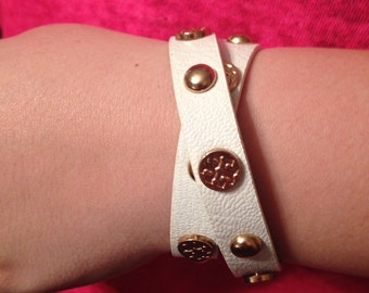 White double wrap leather bracelet with gold accents.