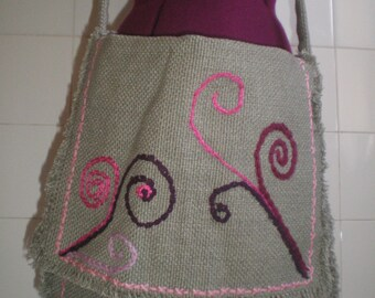Embroidered bag with pink lining.