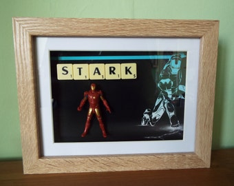 Tony Stark as Iron Man Hasbro action figure with Scrabble tiles in a frame