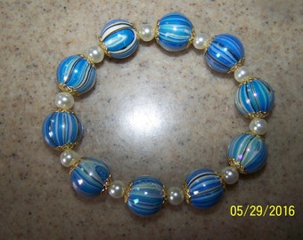 """Beautiful 7"""" blue swirl acrylic beads and gold tone spacers and pearl looking beads"""