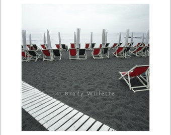 Beach chairs and white umbrellas on black beach with white boardwalk against a black beach in Italy