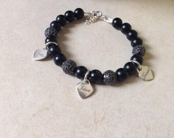 Black bracelet with silver hearts.
