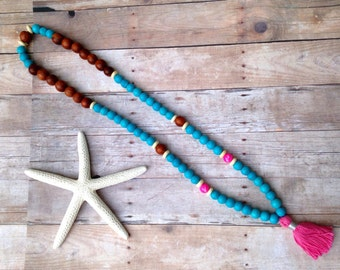Long Pink, turquoise and wooden bead pink tassel necklace.