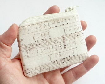 mini zipper pouch. music notes score. cream white hearing aid earbud pouch. jewelry case travel. safety pin flash drive memory card case
