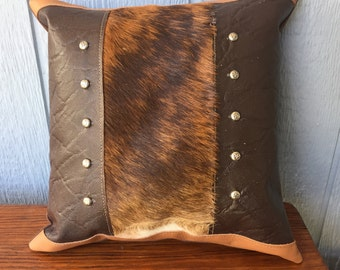 Hair on cowhide fur inset and leather pillow with decorative studs