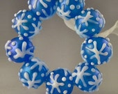 a set of 9 rounds in transparent blue with iridescent pixie dust & raised snowflakes handmade lampwork glass beads - Let It Snow