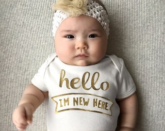 hello i'm new here . onesie . white with shimmery gold lettering