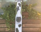 Long-faced Spotted Cow On Plank