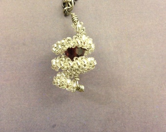 Silver beaded spiral pendant with maroon inner bead on dark silver chain