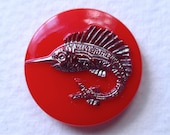 Glass swordfish button, vintage.  It features a silver swordfish, pressed glass & silver lustre, 2 hole sew-thru.  c 1960's.