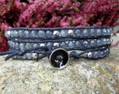 Handmade wrap bracelet with grey semiprecious jade and hematite beads on a black waxed cotton cord