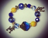 "Arm Candy. ""Pampered Poodle"" Yellow and Royal Blue SGRHO stretch Charm bracelet. Sigma Gamma Rho inspired."