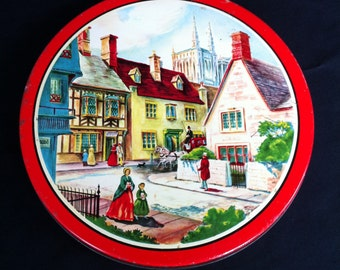A Red Round Flat Tin With A Victorian Scene/Village