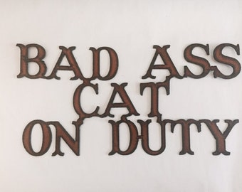 Bad Ass Cat on Duty sign made out of rusted metal