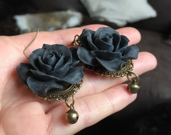 Earrings with big black roses and jinglebells. Bronze materials.