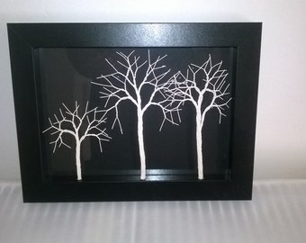Ivory wire trees in a black wooden picture frame.
