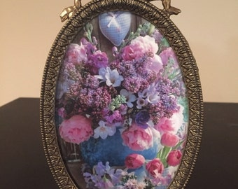 Vintage oval frame with ribbon top filled with bouquet of purple flowers.