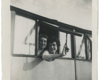 Vintage snapshot photograph of two women looking out of an open window