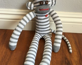 Gray striped sock monkey plush doll with pink heart