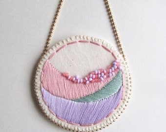 Hand embroidered necklace in geometric pastel pink green and lavender with glass beads on bright cream muslin and matte gold ball chain