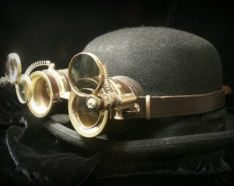 Steampunk goggles in dark brown leather and brass with four moveable lenses.