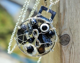 Black Round Whimsical Infinity, MUSKOKA STONE wire wrapped pendant is made with sterling silver wire, glass, resin, ceramic and pewter beads