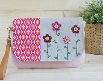 Wrist purse with flap decorated with printed fabric and application of flowers
