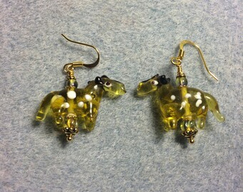 Translucent greenish amber spotted lampwork horse bead earrings adorned with olive green Czech glass beads.